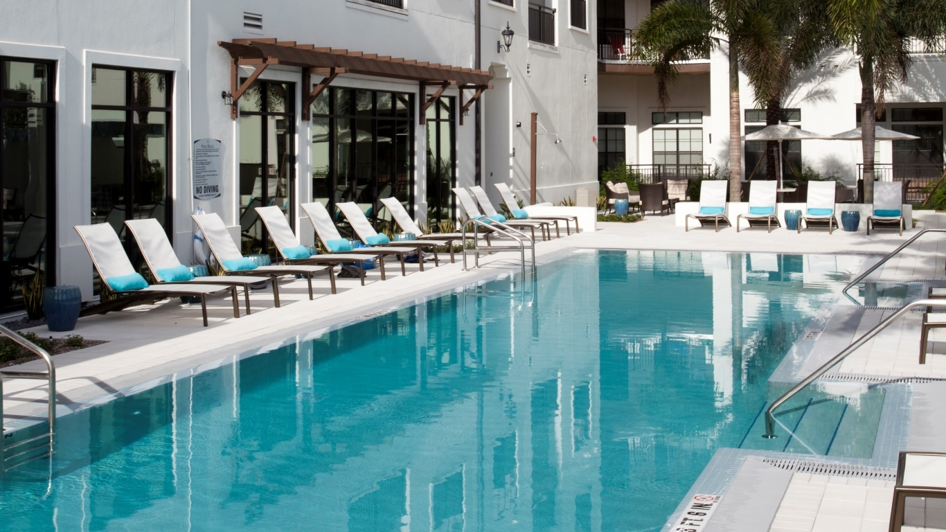 azul resort style pool with chaise lounge chairs, umbrellas and view of apartment building nearby - jefferson apartment group
