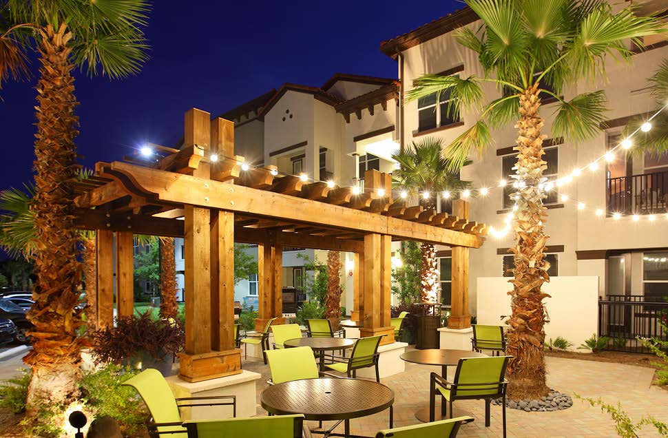 jefferson westshore outdoor living area at night with tables, chairs, pergola and view of apartment building with balconies in the background - jefferson apartment group