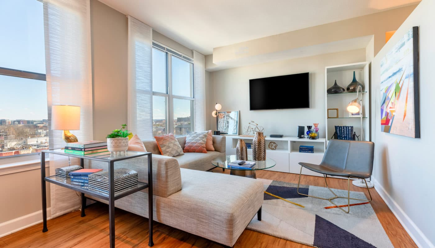 jefferson marketplace living area with couch, flat screen tv, bookshelves and large windows - luxury apartments in washington dc
