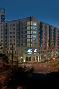 exterior view of 420 east building at night with trees, streetlights and a cityview in the background - jefferson apartment group