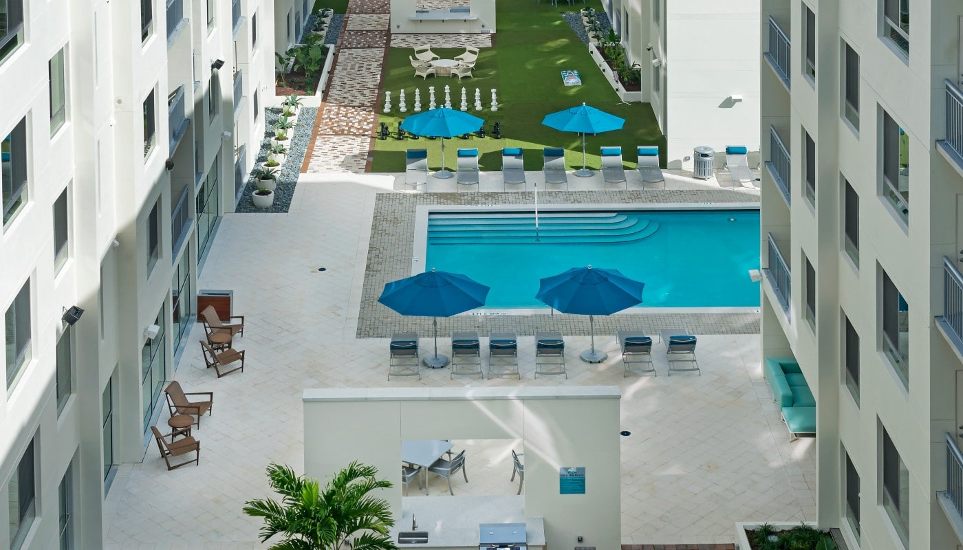 420 east aerial view of outdoor living area, chess board, pool, and apartment buildings and balconies - jefferson apartment group