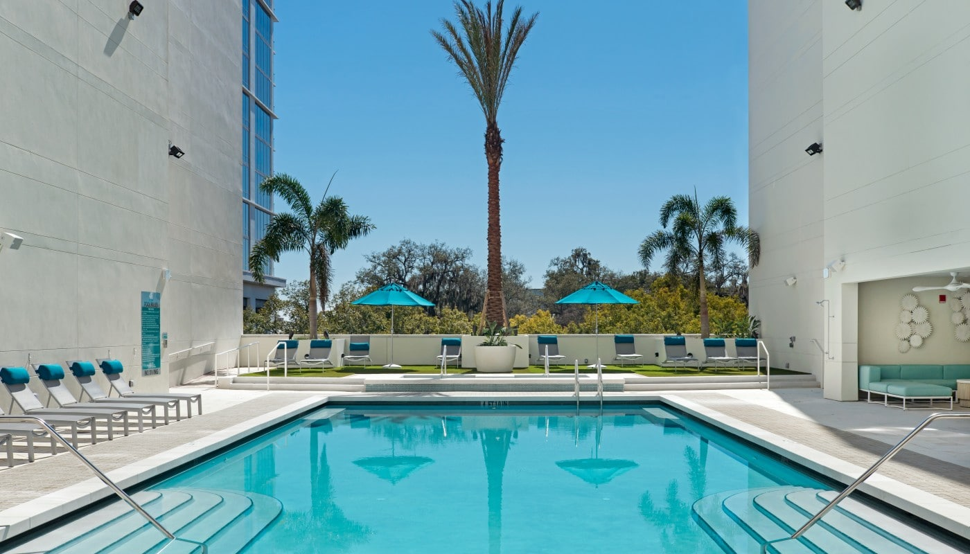 420 east resort style pool with chaise lounge chairs, palm trees, social seating and view of wooded area in the background - jefferson apartment group