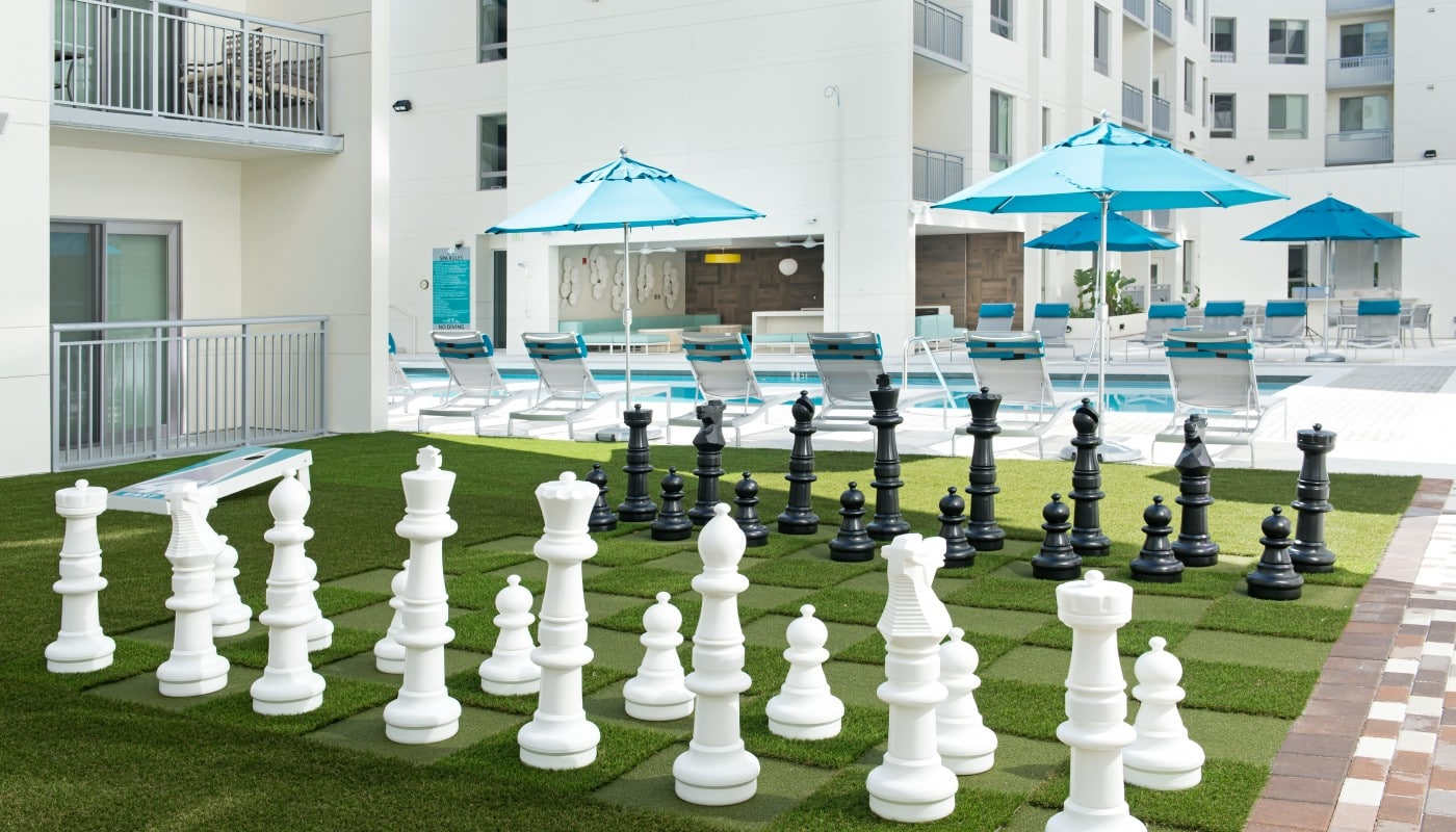 420 east large outdoor chess board with view of pool, chaise lounge chairs and umbrellas in the background - jefferson apartment group