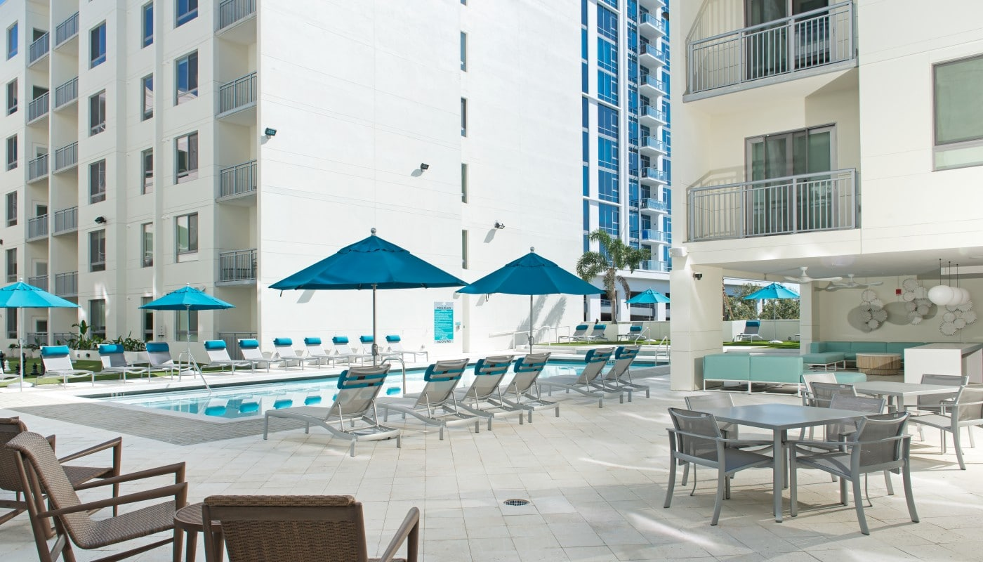 420 east outdoor lounge with pool, social seating, tables, chairs, and view of apartment building with balconies in the background - jefferson apartment group
