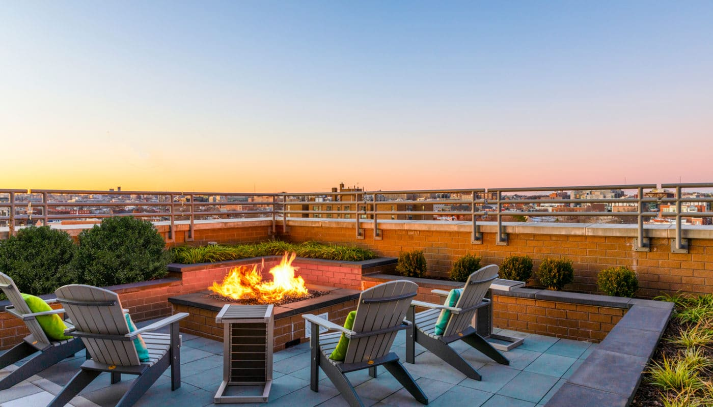 rooftop lounge with social seating, fire pit and view of the city - jefferson marketplace luxury apartments in washington dc