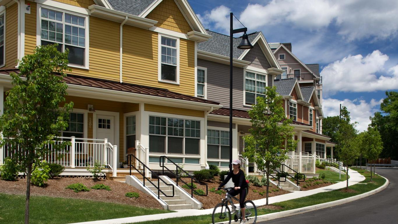 arlington 360 exterior view of town homes, with sidewalks, a person riding their bicycle and green landscaping - jefferson apartment group