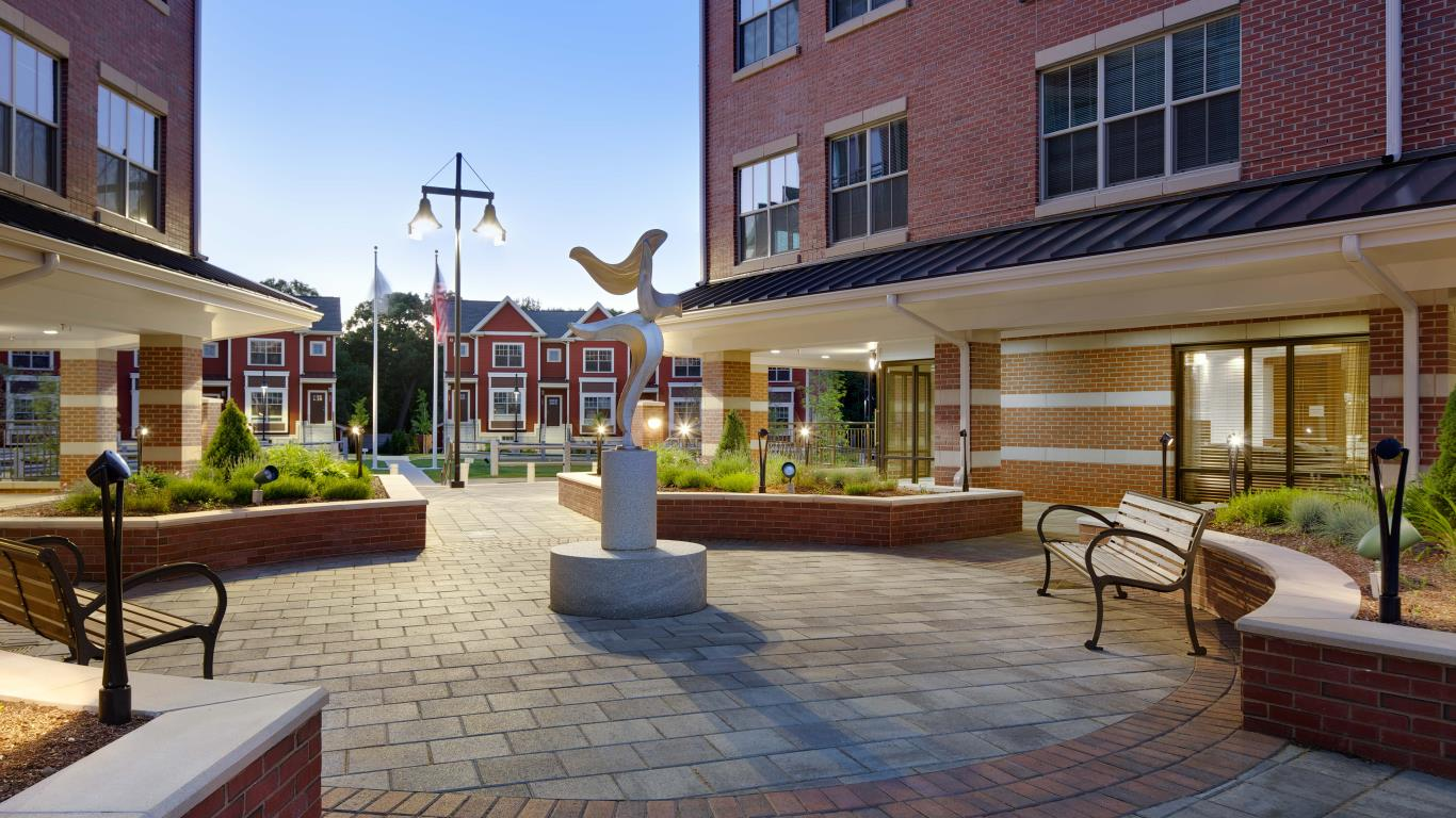 arlington 360 courtyard with art sculpture, bench seating and view of apartment buildings in the distance - jefferson apartment group