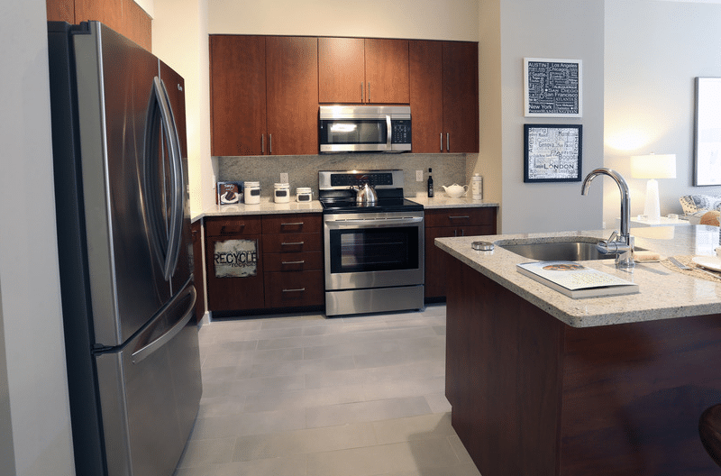 asher kitchen with stainless steel appliances, espresso cabinetry, granite countertops, modern artwork and view of living area - jefferson apartment group