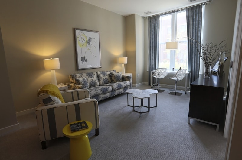 asher living area with couch, side chairs credenza, end tables, large windows and modern artwork - jefferson apartment group