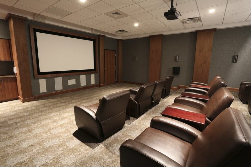 asher media room with large leather chairs, and movie screen - jefferson apartment group