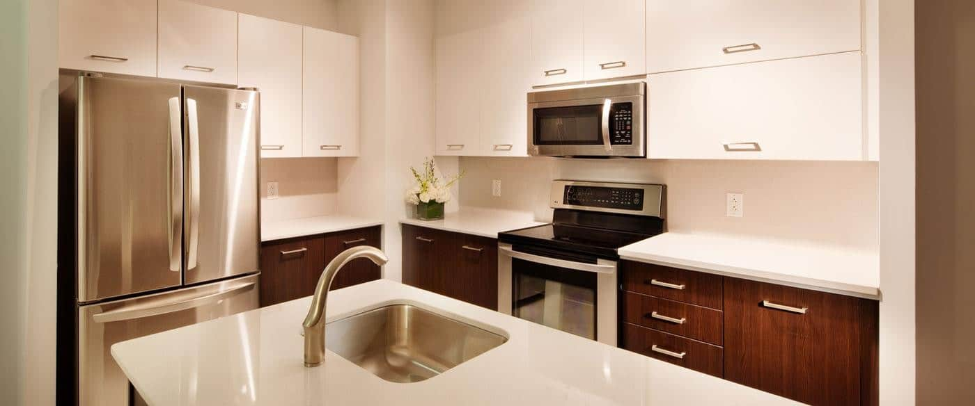 asher kitchen with two toned cabinetry, stainless steel appliances and quartz countertops - jefferson apartment group