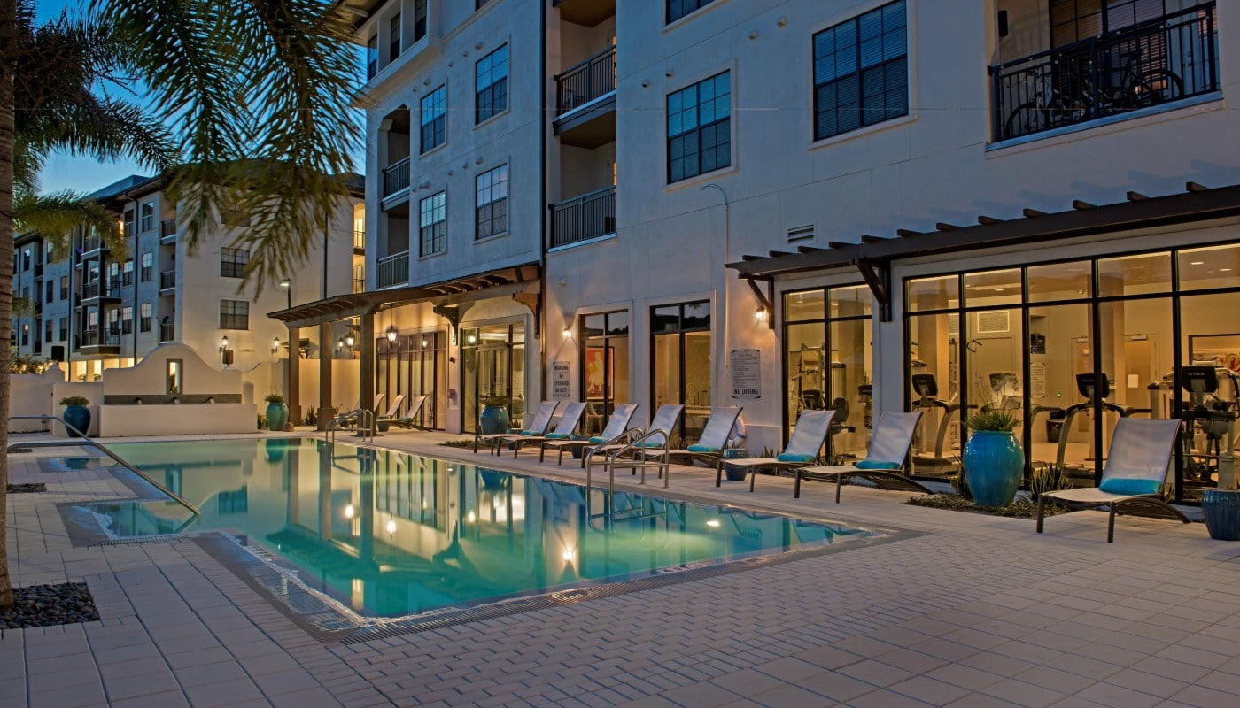 azul resort style pool at night with chaise lounge chairs, view of fitness center and apartment building in the background - jefferson apartment group