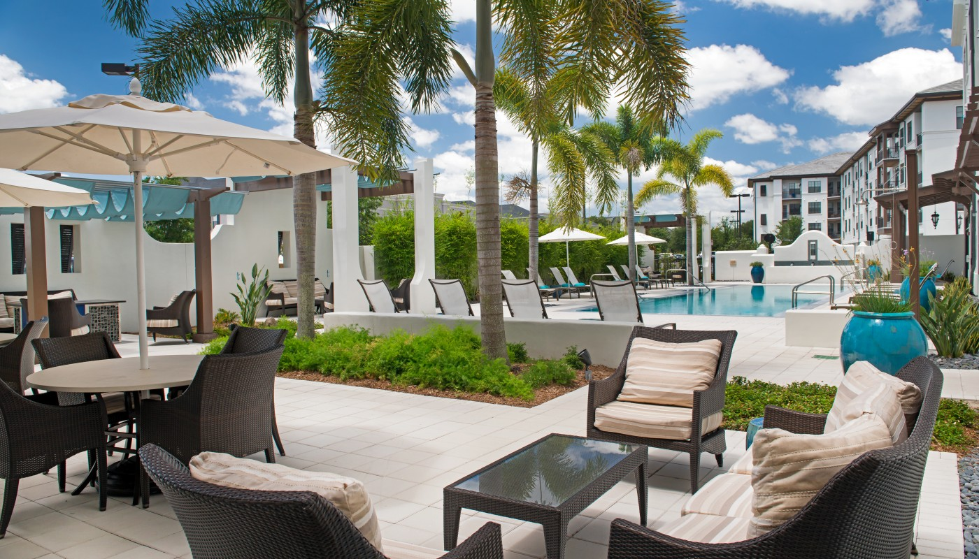 azul outdoor lounge with social seating, tables, chairs, umbrellas, palm trees and view of pool and apartment building in the background - jefferson apartment group