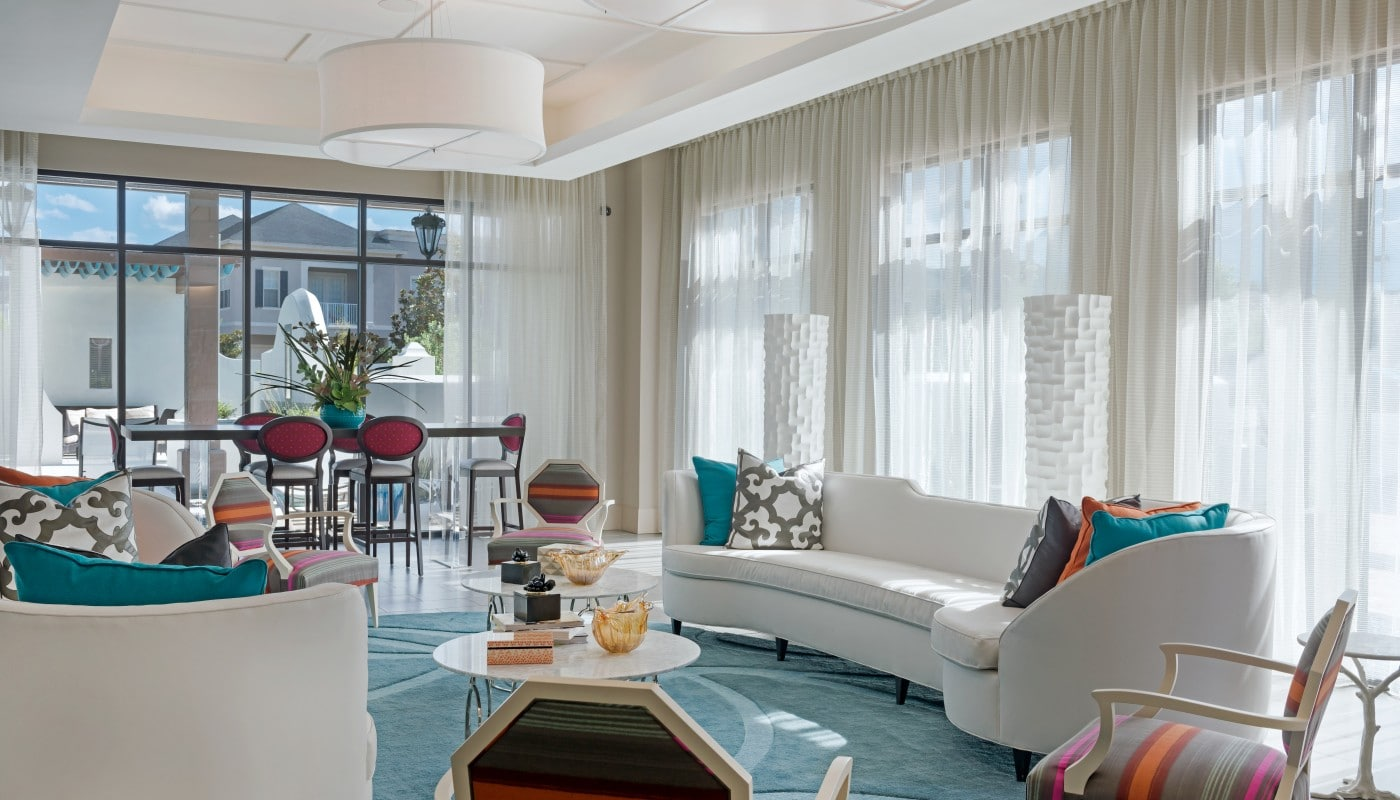 azul resident lounge with social seating, tables, chairs, large windows and modern lighting - jefferson apartment group