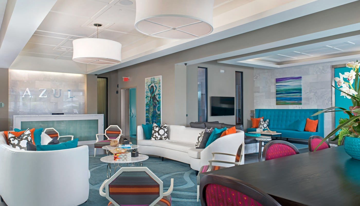 azul lobby with concierge desk, colorful social seating, tables, chairs, and modern lighting - jefferson apartment group