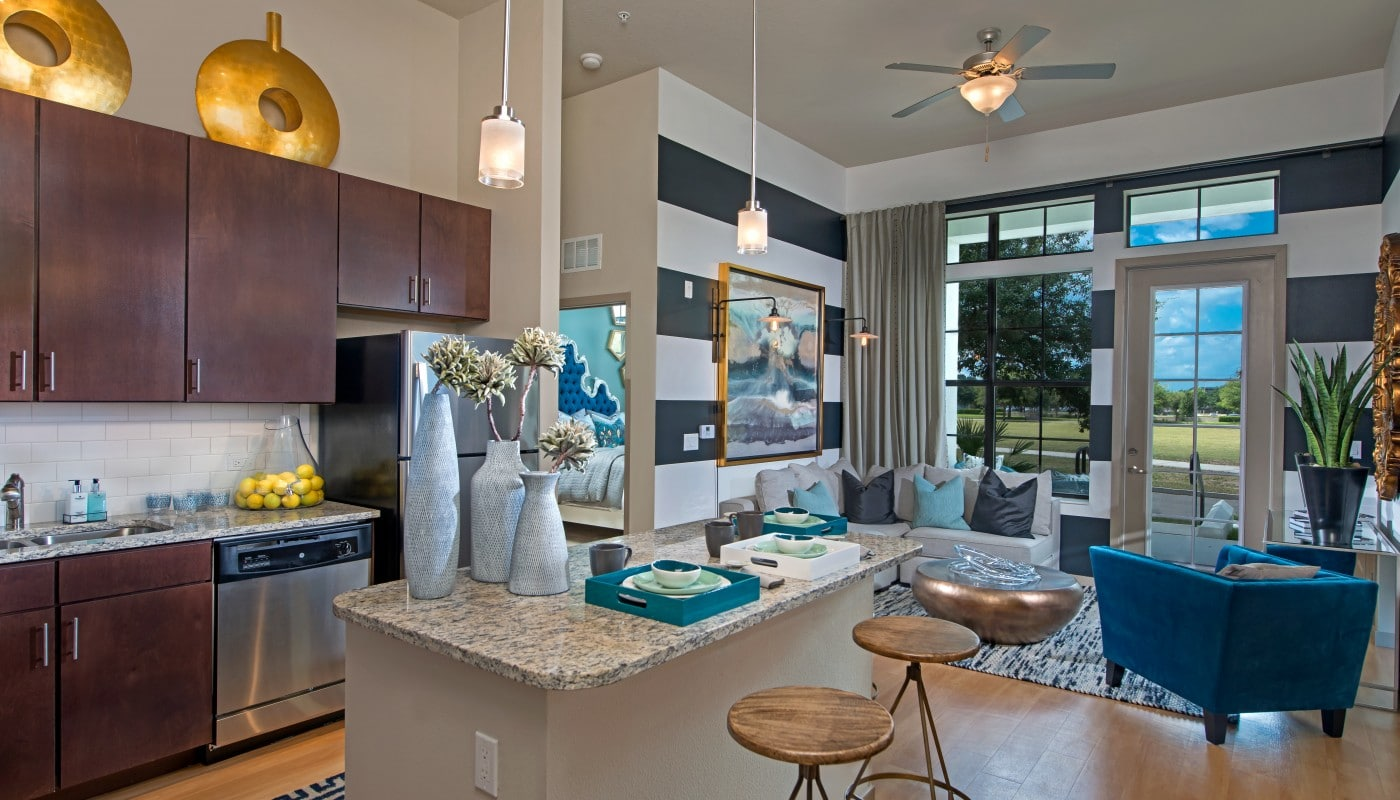 azul living area with couch, side chair, plank flooring, modern artwork and view of kitchen with granite countertops, espresso cabinetry, stainless steel appliances and modern lighting - jefferson apartment group