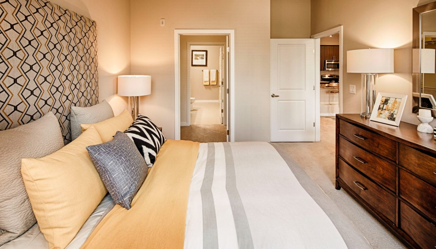 Bedroom with bed, dresser, mirror, night stand, and view of bathroom at jefferson luxury apartments in baltimore