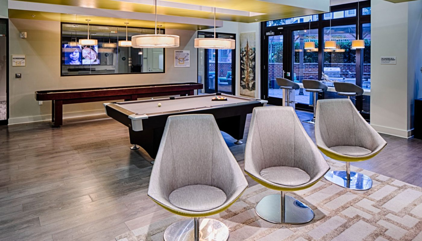 lounge with social seating, tables, flat screen tv, modern artwork, billiards and shuffleboard at jefferson square luxury baltimore apartments