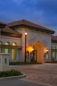 exterior view of jefferson lighthouse place at dusk with palm trees and green landscaping - jefferson apartment group