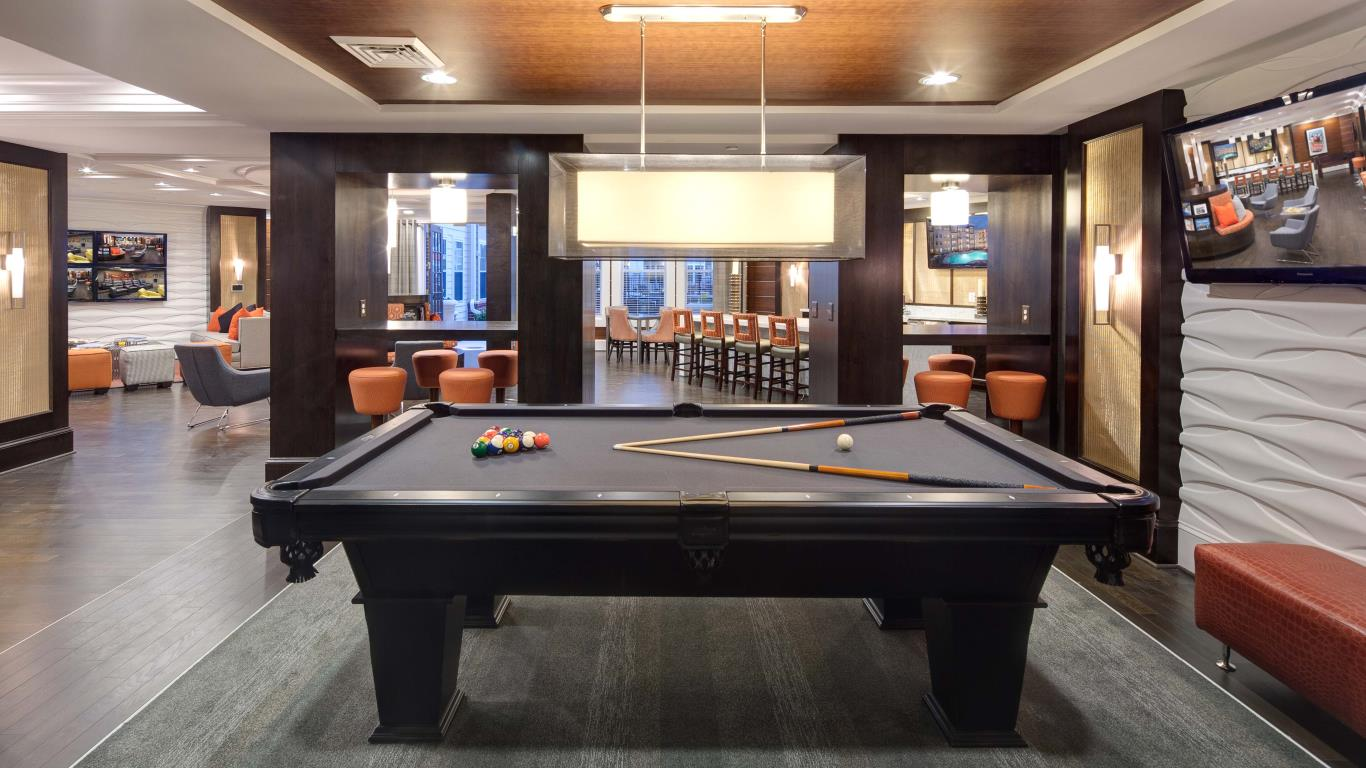 jefferson pointe game room with billiards, social seating, flat screen tv and view of bar area - jefferson apartment group