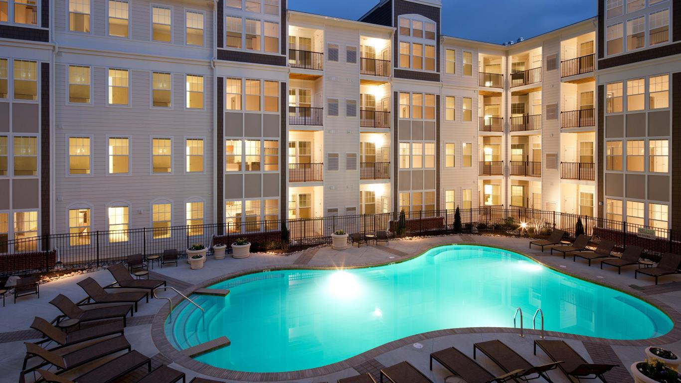 jefferson pointe at west chester resort style pool with chaise lounge chairs, and apartment building in the background - jefferson apartment group
