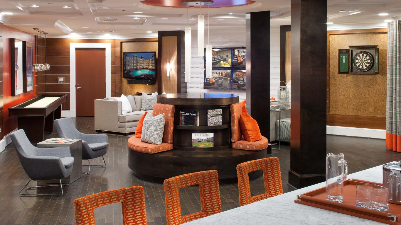 jefferson pointe at west chester resident lounge with fun chairs, couch, dart board, shuffleboard and bar seating - jefferson apartment group