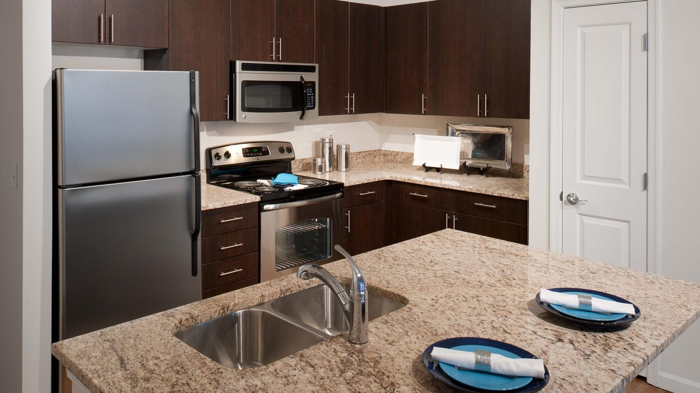 jefferson pointe at west chester kitchen with granite countertops, stainless steel appliances, breakfast bar with place settings and espresso cabinetry - jefferson apartment group