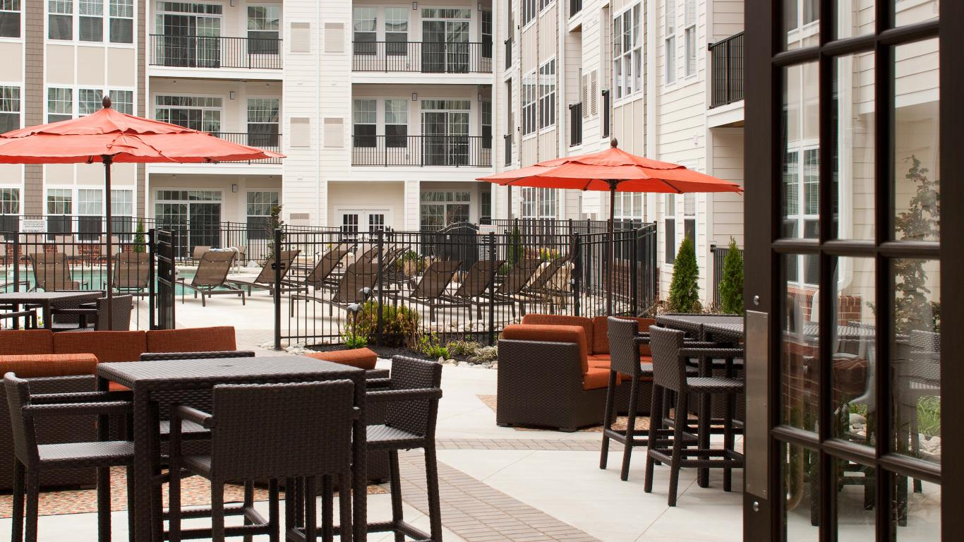 jefferson pointe at west chster outdoor lounge with tables, chairs, social seating and view of pool and apartment building in the background - jefferson apartment group