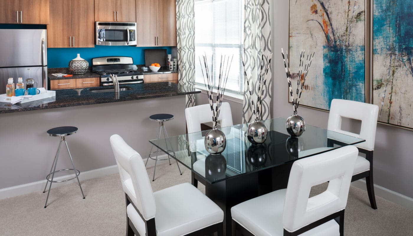arlington 360 dining area with table, four chairs, modern artwork and view of kitchen with granite countertop and stainless steel appliances - jefferson apartment group