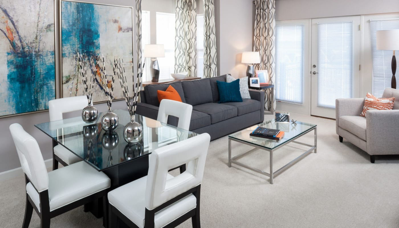 arlington 360 living area with couch, coffee table, side chair, french doors and dining table with four chairs - jefferson apartment group