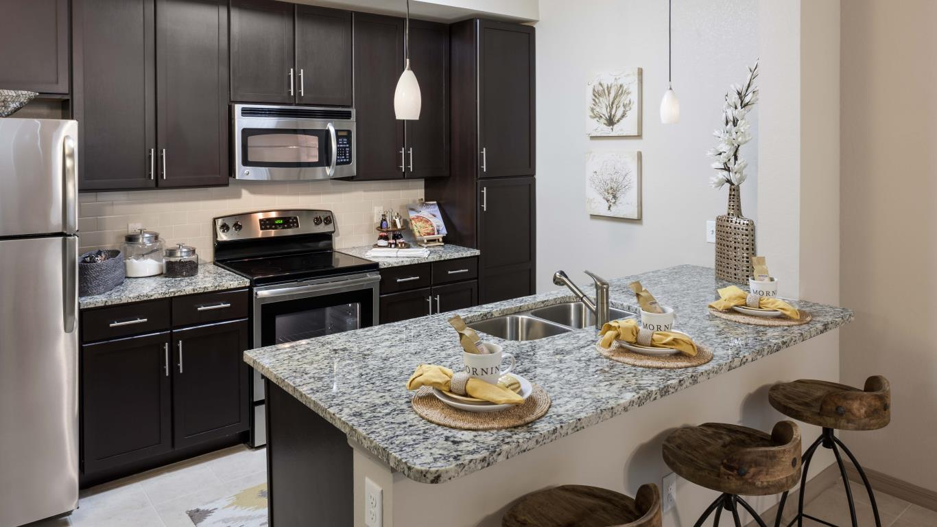 jefferson monterra kitchen with espresso cabinetry, granite countertops, stainless steel appliances and tiled flooring - jefferson apartment group