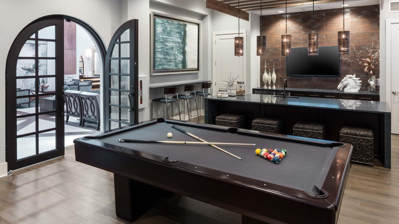 jefferson montera game room with billards. bar seating, modern artwork, and large french doors - jefferson apartment group