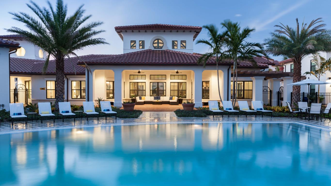 jefferson montera resort style pool with chaise lounge chairs and resident club house in the background - jeffferson apartment group