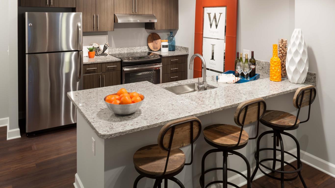 jefferson marketplace kitchen with plank flooring, granite breakfast bar, stainless steel appliances and modern artwork - jefferson apartment group