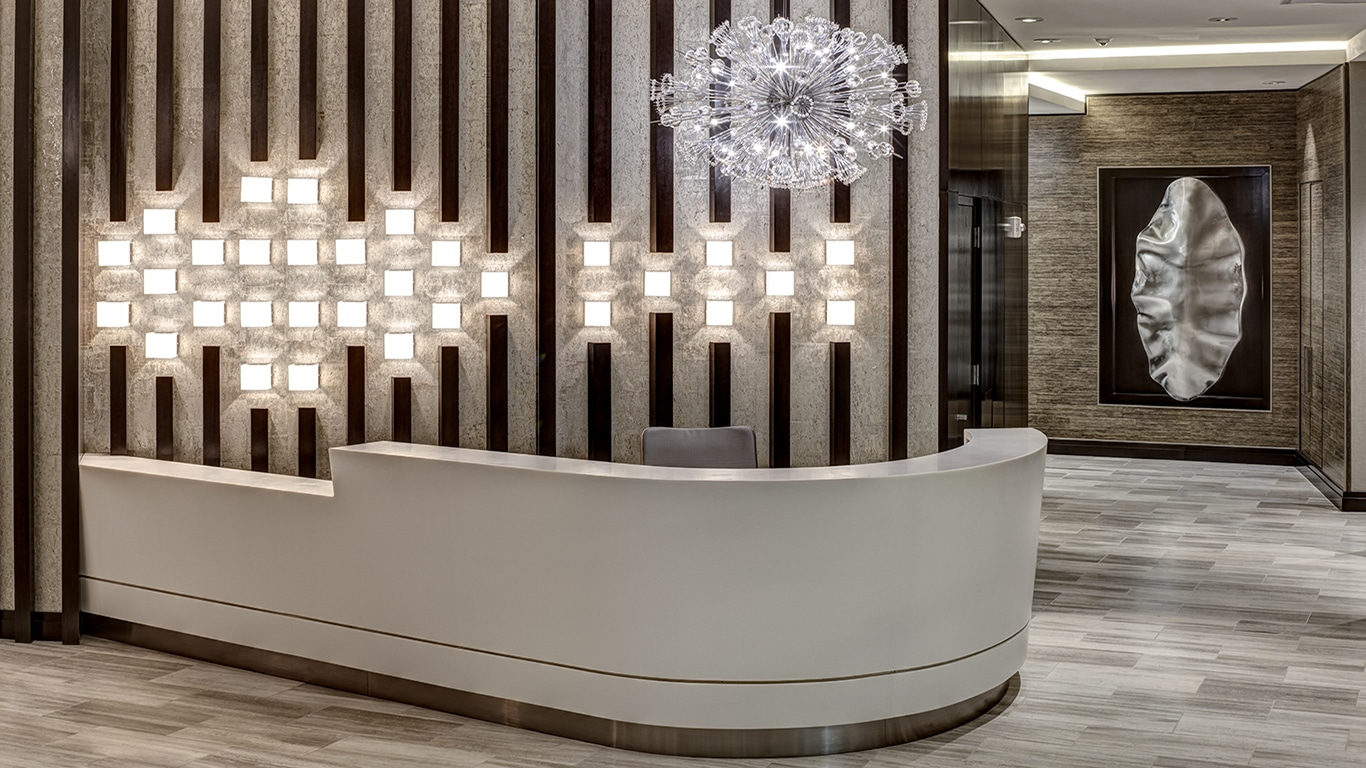 tellus concierge desk with modern arwork and lighting - jefferson apartment group