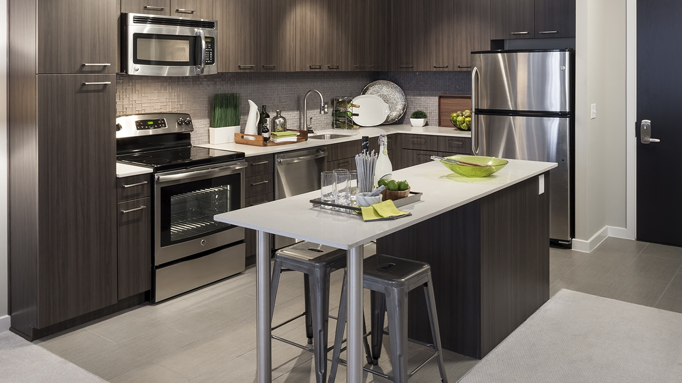tellus kitchen with stainless steel appliances, tiled flooring, kitchen island, and quartz countertops - jefferson apartment group