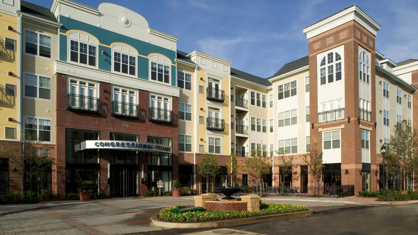 residences at congressional village exterior showing a four story building with circle driveway and large fountain - jefferson apartment building
