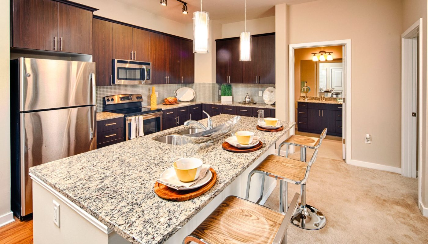 Kitchen with stainless steel appliances, modern cabinetry, and granite island at Jefferson square luxury Baltimore apartments