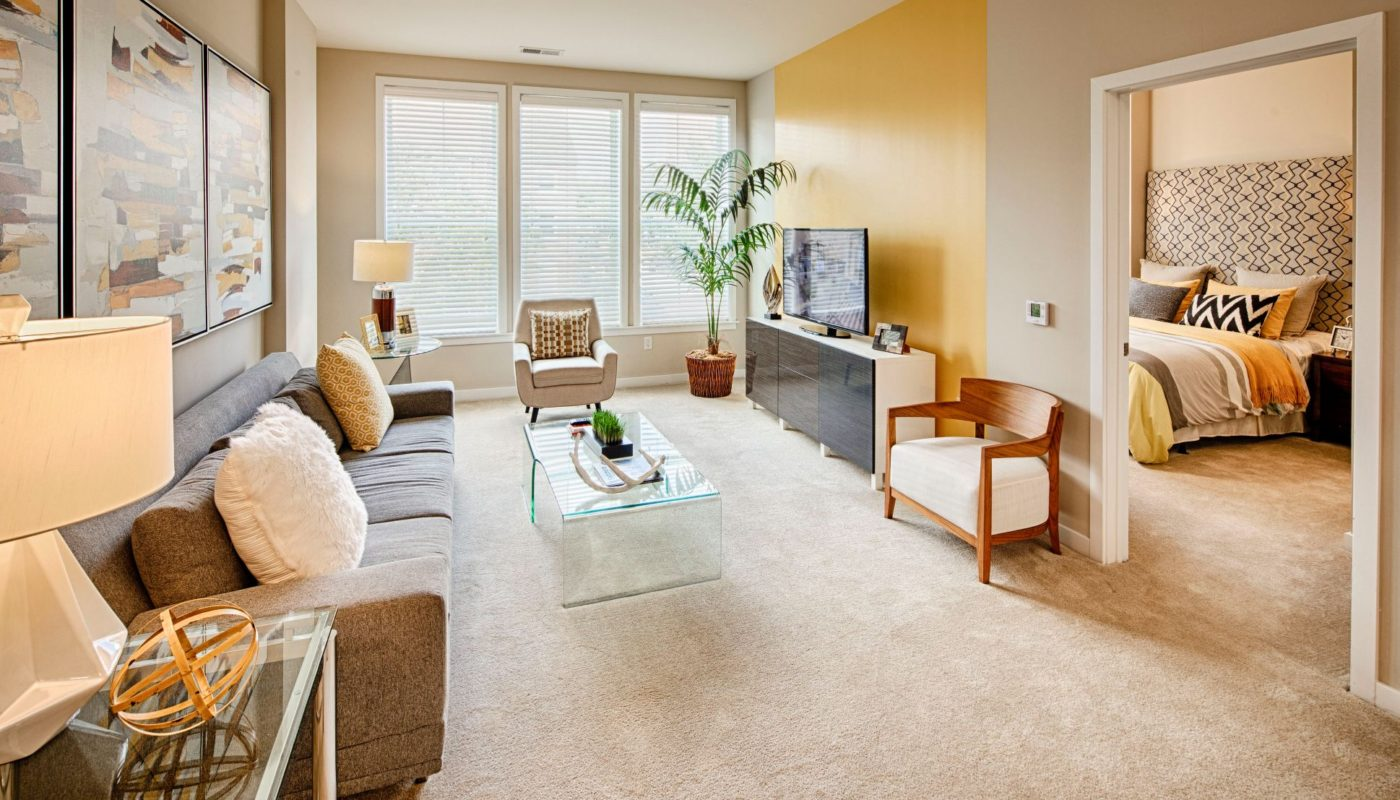 living space with sofa, coffee table, end table, chairs, oversized windows, tv, credenza and view of bedroom at Jefferson square luxury Baltimore apartments