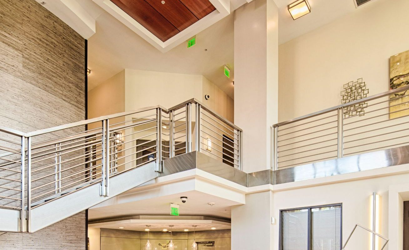 lobby lounge with concierge desk, chandeliers, grand staircase and social seating at Jefferson square luxury Baltimore apartments
