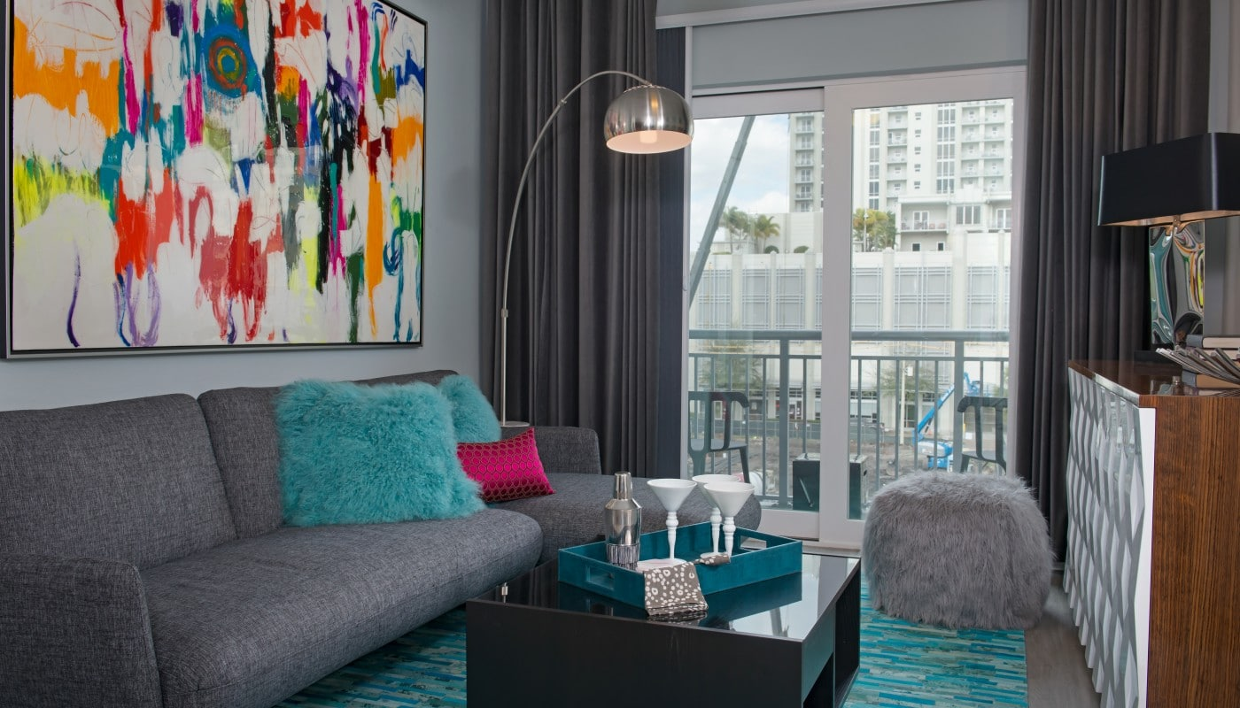 living area with couch, coffee table, fuzzy ottoman, credenza, modern lighting and view of balcony - jefferson apartment group