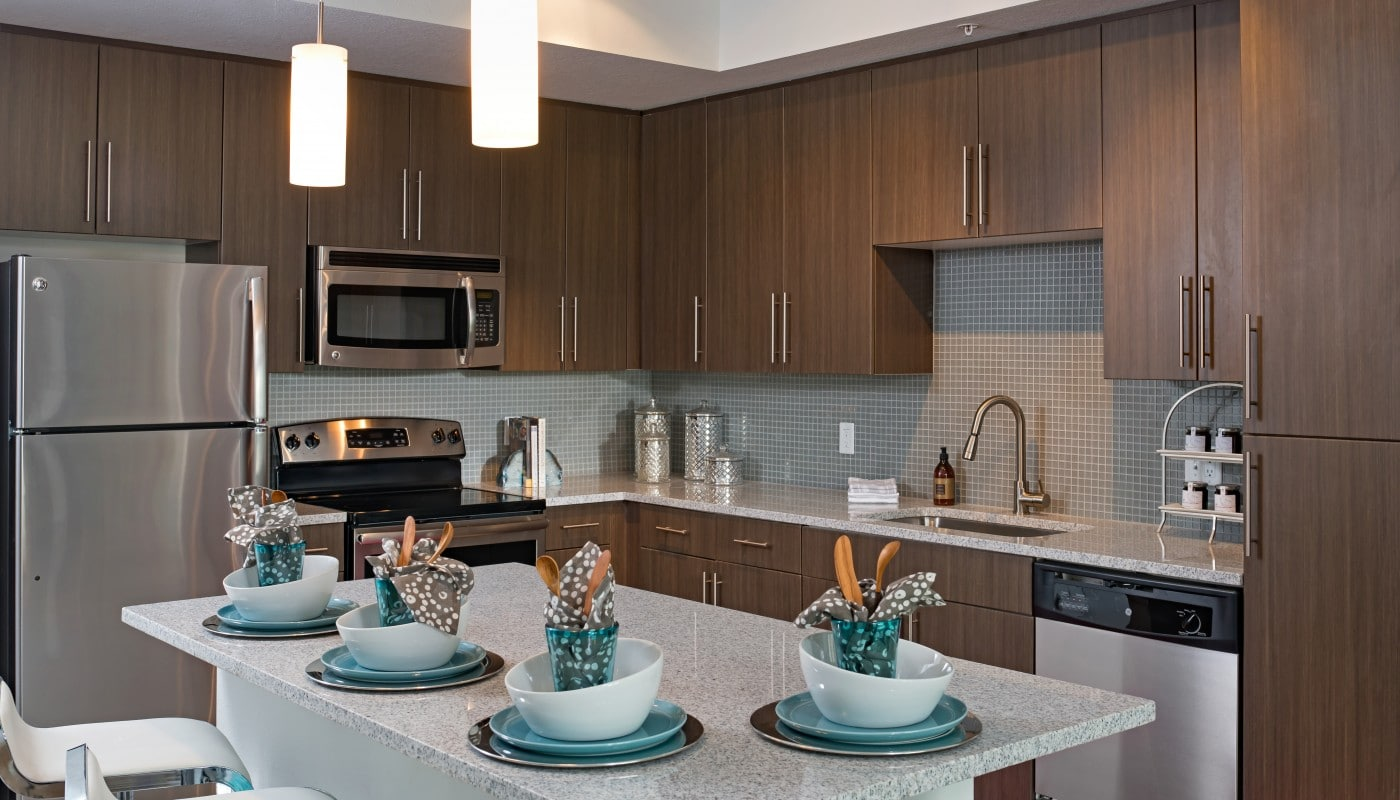 kitchen with granite island, dark wood cabinetry, modern lighting, stainless steel appliances and a tile backsplash - jefferson apartment group