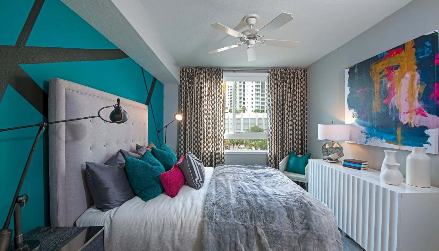 bedroom with bed, dresser, night stand, modern artwork, ceiling fan and large window - jefferson apartment group