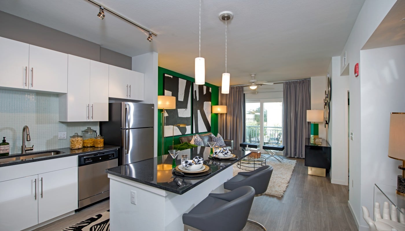 kitchen with large island, quartz countertops, stainless steel appliances, white cabinetry, modern lighting and view of living area and balcony - jefferson apartment group