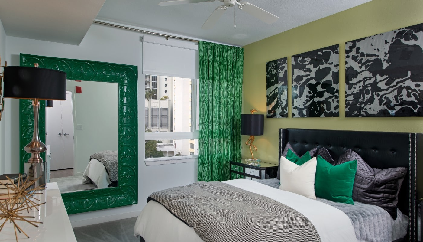 bedroom with bed, night stands, dresser, large mirror and modern artwork - jefferson apartment group