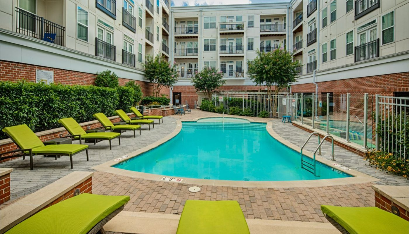 pool in courtyard with social seating, chaise lounge chairs, and view of balconies at jefferson square luxury baltimore apartments