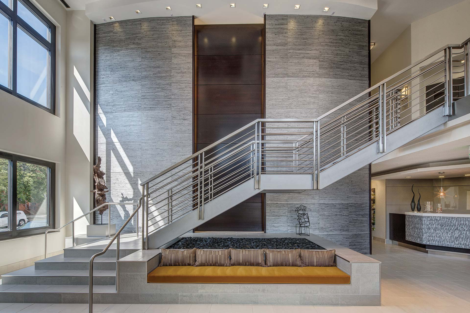 jefferson square lobby with a grand staircase, large windows, concierge desk and bench seating - jefferson apartment group