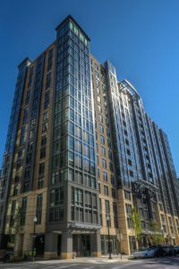 exterior view of tellus high rise apartment building with cars parked nearby - jefferson apartment group