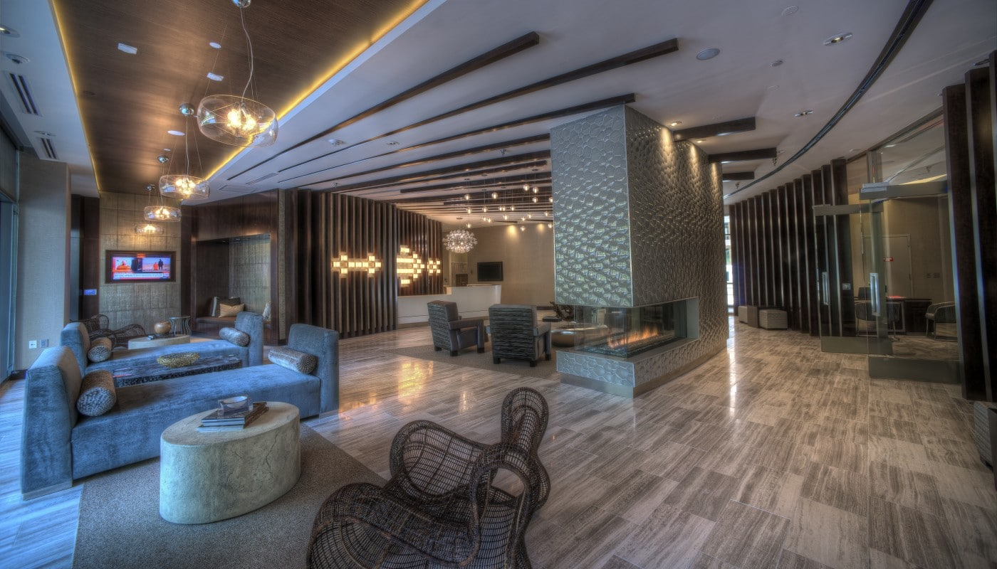 tellus lobby with fireplace, social seating, modern lighting, concierge desk, flat screen televisions and modern artwork - jefferson apartment group