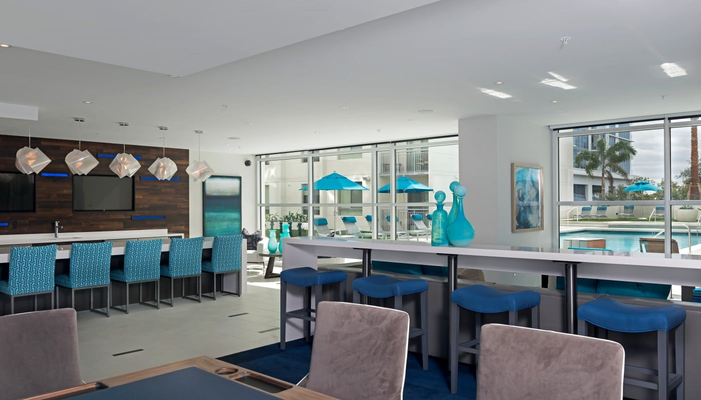 club house with bar seating, poker table, view of pool, large windows, modern artwork and modern lighting - jefferson apartment group
